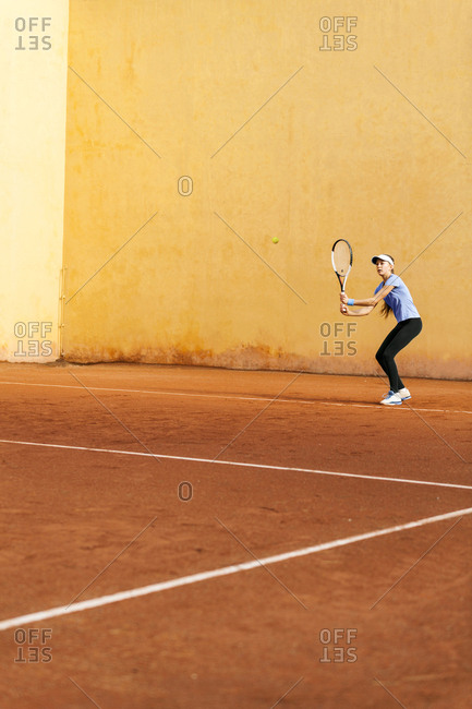 Teenage girl playing tennis on court