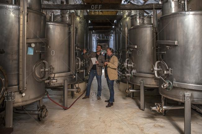 Business people talking in front of fermentation tanks