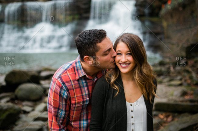 Man kissing his fiancee on the cheek outside in nature