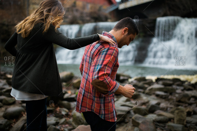 Woman with hand on fiance's shoulder while walking on rocky path in front of waterfall