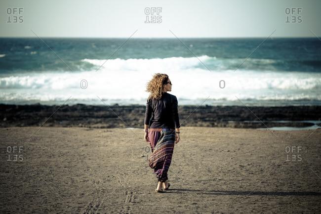 Woman strolling a beach alone