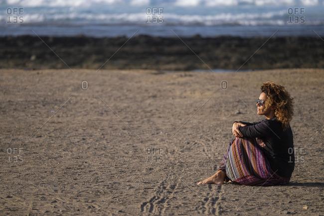 Woman sitting on a beach alone