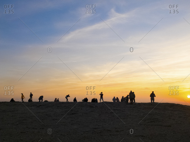 People watching a coastal sunset