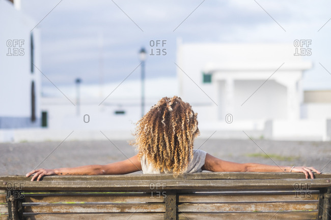 Curly haired woman on coastal bench