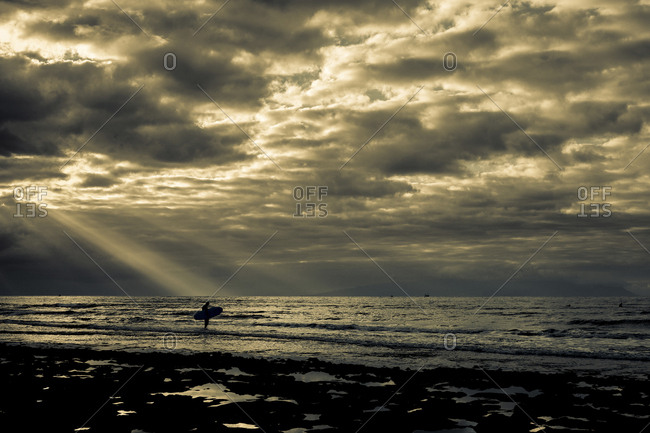 Person with surfboard in coastal sunbeams