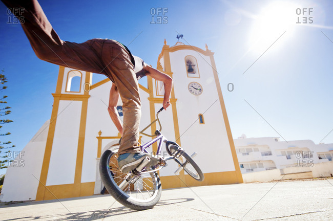 Person doing bike trick by church
