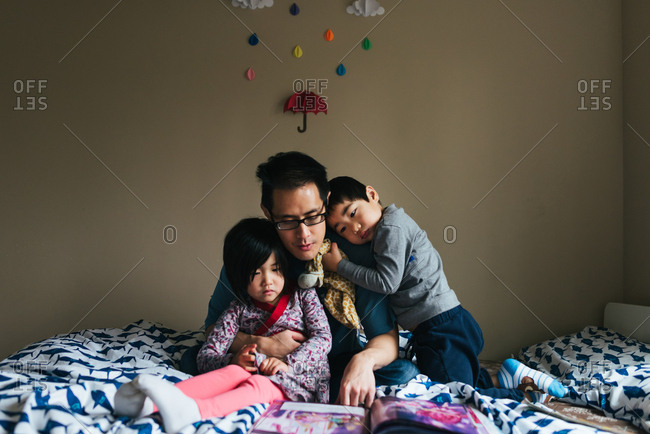 Dad reading with kids on bed