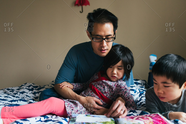 Dad reading with two kids on bed