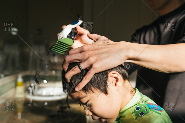 Dad using clippers on boy's hair