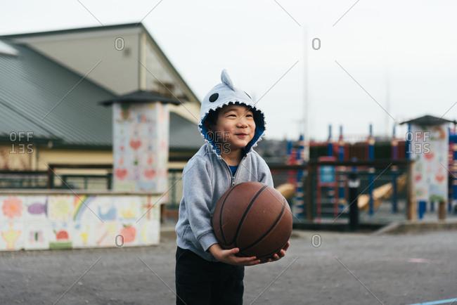 Boy in shark hoodie holding basketball