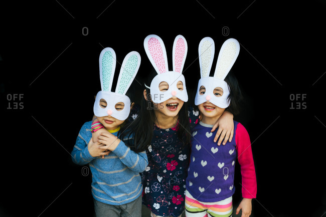 Three happy kids in Easter masks