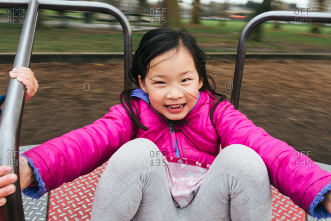 Girl spinning on merry go round