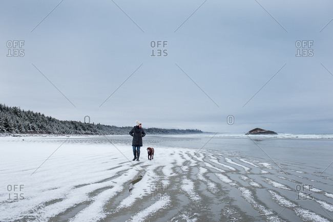 Woman and dog walking winter beach