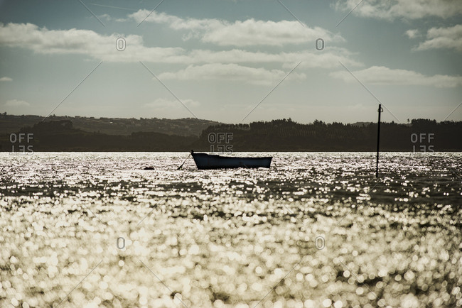 Lagoa de Obidos, Portugal - February, 21, 2015: A boat on shimmering water