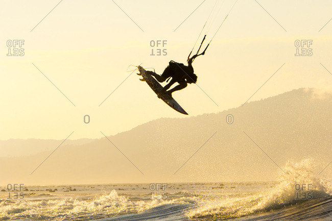 A kite surfer does a big indie grab backside air in remote Indonesia.