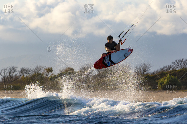 A kite surfer launches an indie grab front side air in remote Indonesia.
