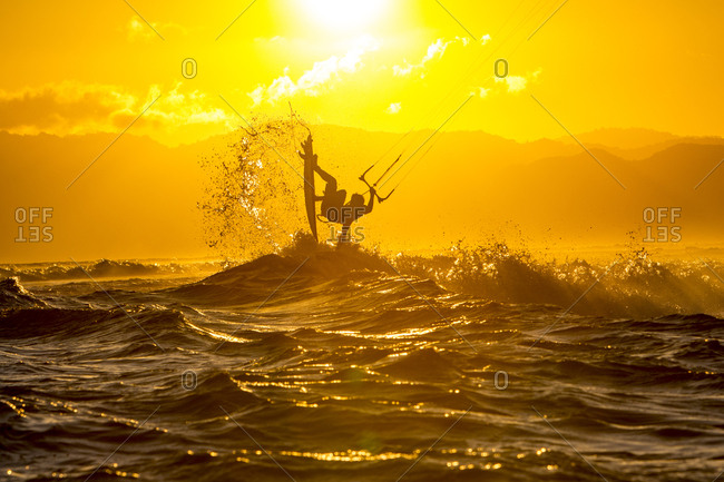 A kite surfer riding in remote Indonesia. golden hour.
