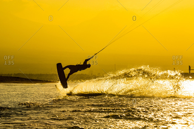 A kite surfer riding in at sunset in java Indonesia. golden hour.