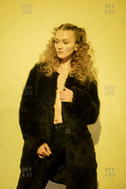 Fashion model with long curly hair wearing a black fur coat