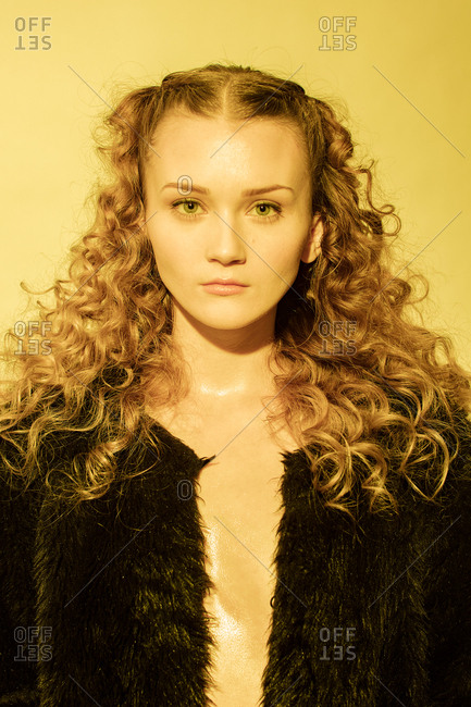 Portrait of a woman with long curly hair wearing a black fur coat