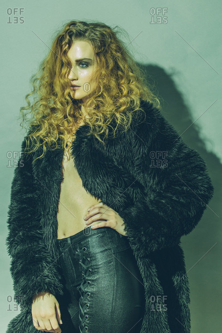 Young woman with long curly hair wearing a black fur coat and leather pants with hand on waist
