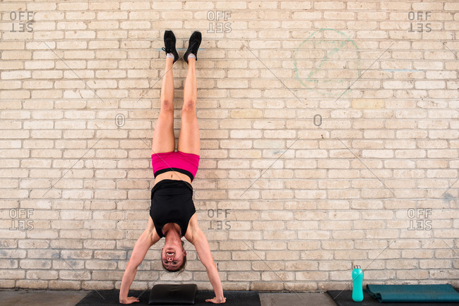 Woman doing a handstand push-up against a brick wall