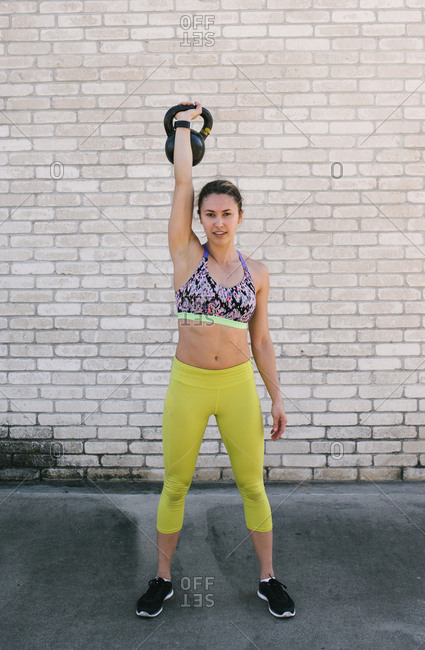 Woman lifting a kettle bell above her head