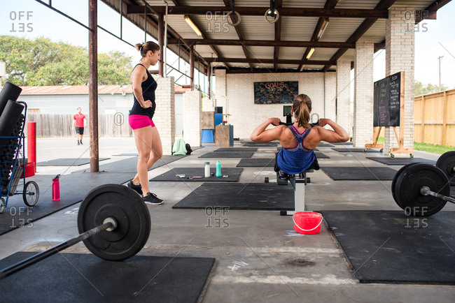 Two women working out in an open-air gym with weights