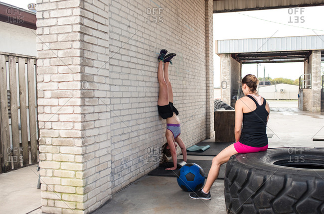 Woman sitting on a tractor tire watching her friend do a handstand push-up