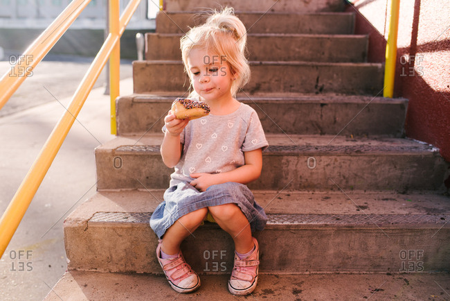 Little girl sitting on steps eating a sprinkled donut