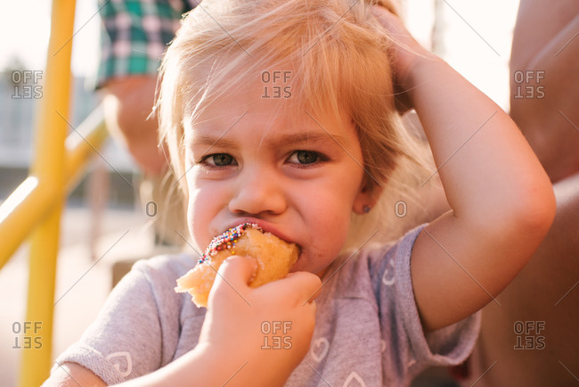 Little girl eating a donut with sprinkles