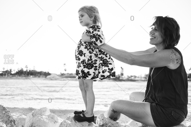 Mother helping her daughter stand on rocks at a beach