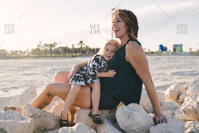 Little girl sitting in her mother's lap on rocks at a beach