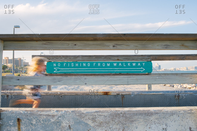 Little girl running past a sign on a wooden walkway at the beach