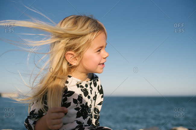 Little girl in a floral dress by the ocean