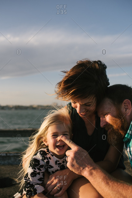 Mom, dad and daughter smiling and embracing on a pier