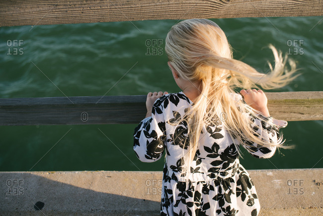 Little girl in a floral dress looking at the ocean from a pier