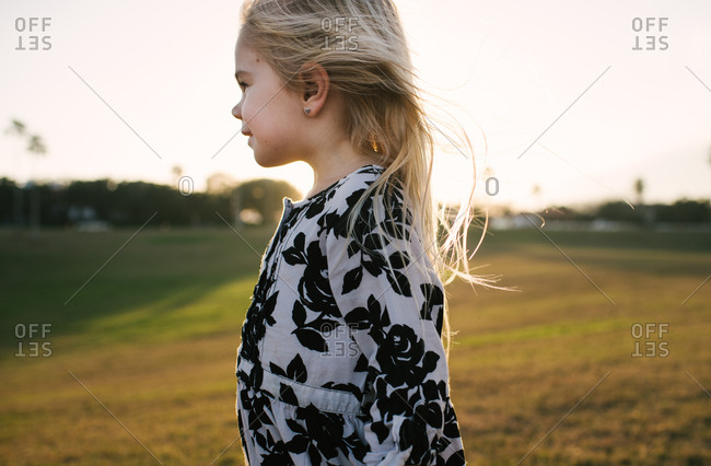 Little girl in a floral dress standing in a field at sunset