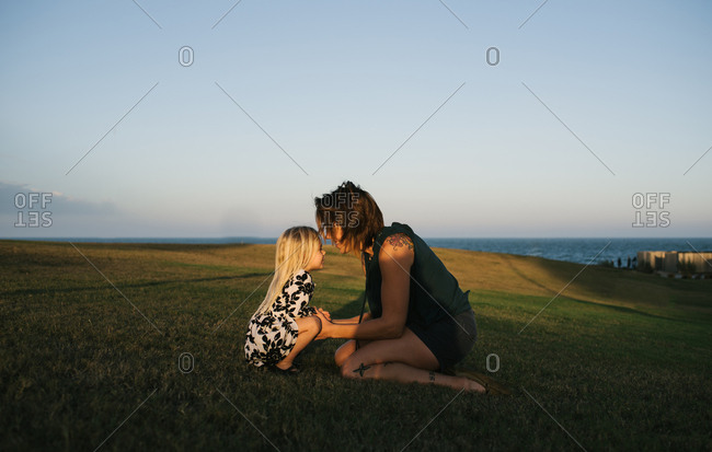 Mother kneeling on a field with her daughter at sunset