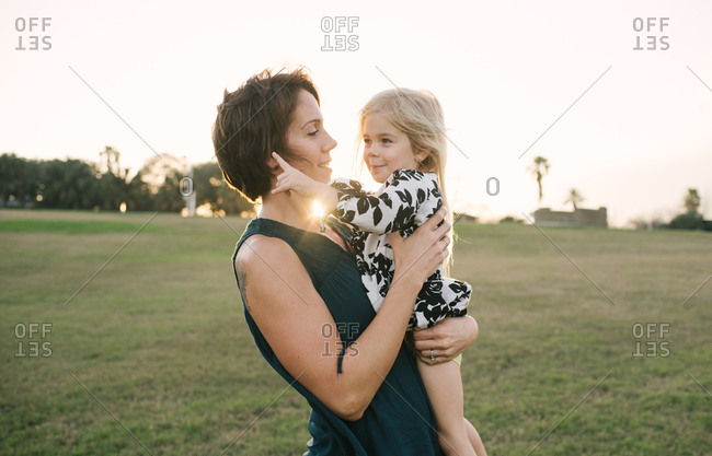 Mother holding her daughter in a field at sunset