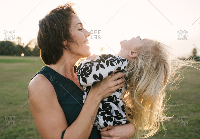 Mother and daughter standing in a field laughing at sunset