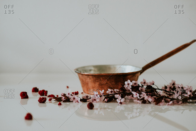 Copper pan with red raspberries and flowers