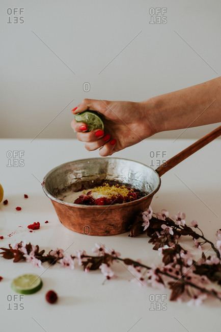 Hand squeezing lime into a pan with sugar and berries