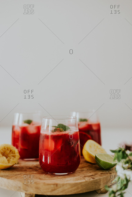 Raspberry cocktails garnished with mint on a wooden tray