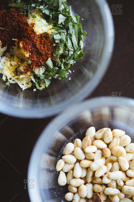 Bowl of pine nuts and a bowl of herbs and spices