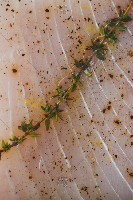 Raw sea bass with a sprig of thyme and seasoning