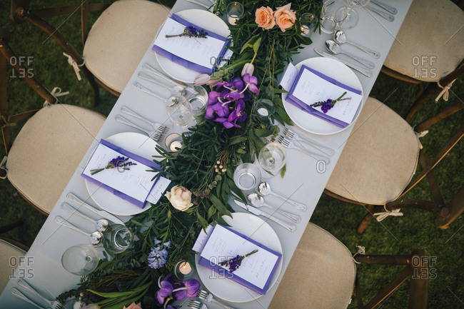 Rustic chairs, floral centerpiece and purple menus at a wedding reception