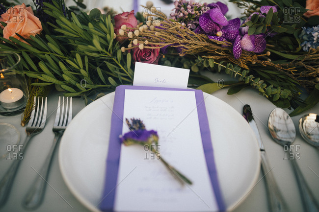 Purple menu and plate and a place setting for a wedding reception