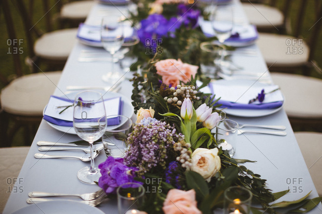 Centerpiece at a wedding reception with purple menus and accents