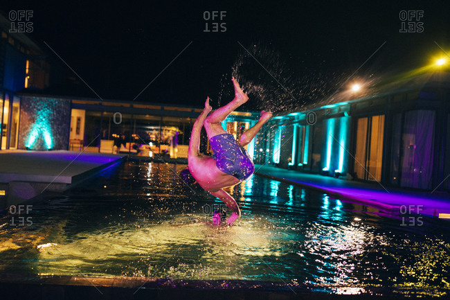 February 20, 2017: Man doing a backflip into a pool with colorful lights at night